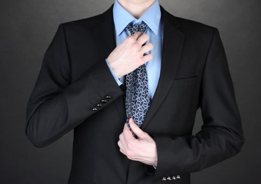 12715797 - businessman correcting a tie on black background