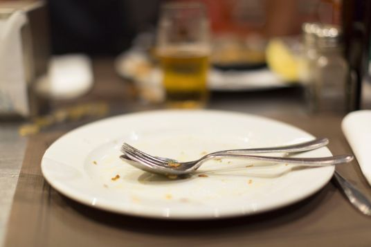 44430749 - empty plate of food after meal on a table